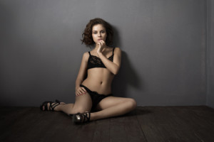 Young girl in black lingerie sitting in front of a gray wall