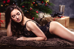 portrait of sensual young woman in a black lingerie over christmas background